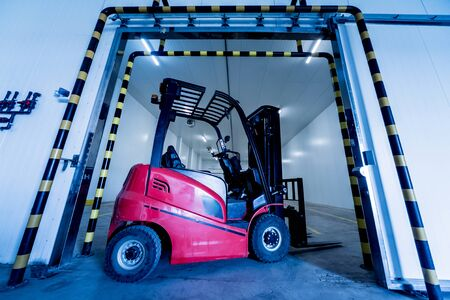 Forklift in a large industrial freezer warehouse. Empty warehouse