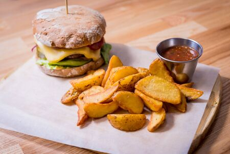 Tasty cheeseburger and chips on the wooden table. Restaurant.