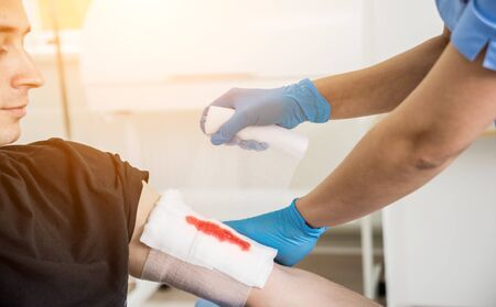 Nurse dressing wound for patient's hand with deep skin cutting. Medical background Stock fotó