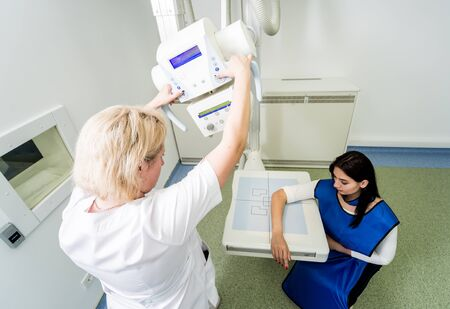 Radiologist and patient in a x-ray room. X-ray of human hand.