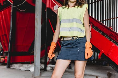 Woman-volunteer sorting trash at modern recycling plant. Separate garbage collection. Trash sorting. Background