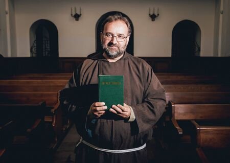 A monk in robes with holy bible in their hands praying in the church