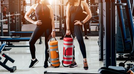 Athletic young women training with sandbags at gray background. Crossfit center. Fitness concept. Фото со стока