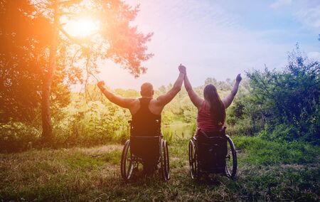 Handicapped couple resting in the forest near lake. Wheelchairs in the forest on the natural background. Camping. Summertime Foto de archivo