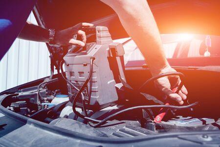 Accumulator charging. Hands and terminal. Car and repair. Imagens