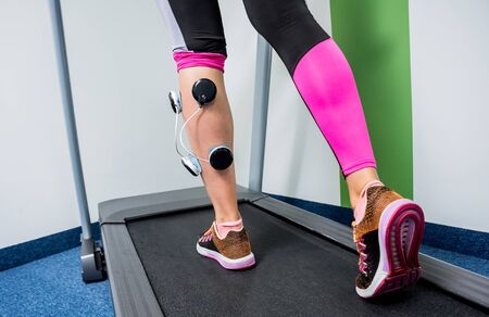 Young sports woman with electrostimulator on the muscles of the legs. Fitness training with an electrostimulator. Physiotherapy.