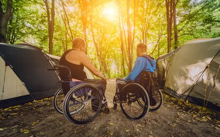 Two disabled men resting in a campsite with friends. Wheelchair in the forest