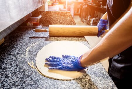 The process of making pizza. Hands of chef baker making pizza at cafe kitchen