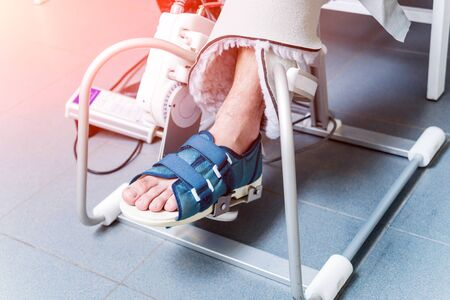 Patient on CPM machines, continuous passive range of motion. Device to provide anatomically correct motion to both the ankle and subtalar joints. Foot's rehabilitation after injured Stock fotó