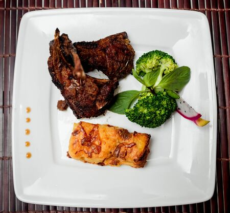 Roasted meat on the white plate. Barbecue. Restaurant. Banco de Imagens