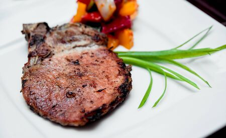 Roasted meat on the white plate. Barbecue. Restaurant Banco de Imagens - 143002841