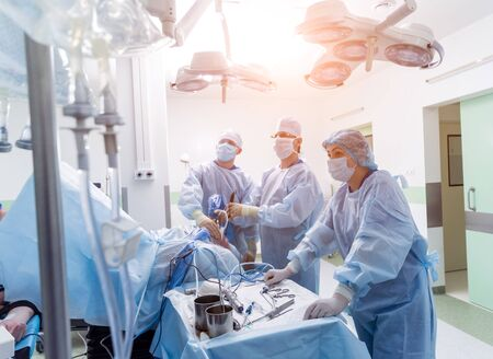 Arthroscope surgery. Orthopedic surgeons in teamwork in the operating room with modern arthroscopic tools. Knee surgery. Hospital background