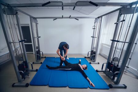 Concept of rehabilitation . Beautiful young woman doing exercises on mat under supervision of physiotherapist. Exercise therapy