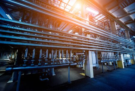 Interior of modern natural oil factory. The piping, pumps and motors. Industry background
