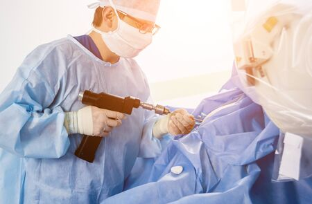 Arthroscope surgery. Orthopedic surgeons in teamwork in the operating room with modern arthroscopic tools. Hospital background