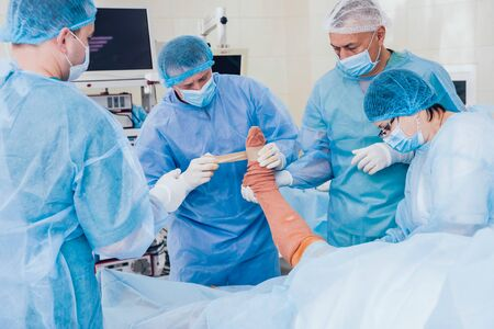 Process of trauma surgery operation. Group of surgeons in operating room