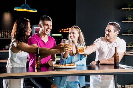 Cheerful friends in the pub. Drinking beer, wine and whisky Standard-Bild