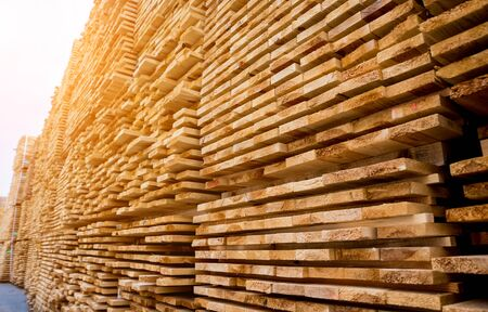 Stack of natural rough wooden boards. Wooden boards, lumber, industrial wood.