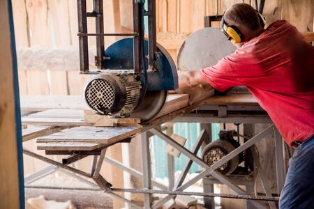 Modern sawmill. A carpenter works on woodworking the machine tool. Industrial background