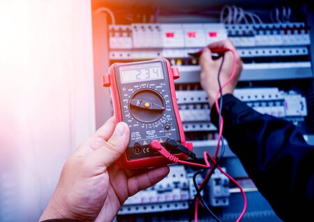 Electrical measurements with multimeter tester. Modern electrical background.