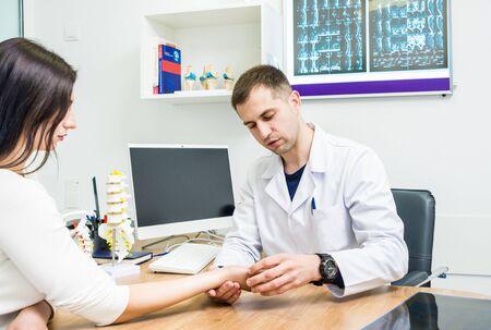Traumatologist examining patient hands in modern hospital