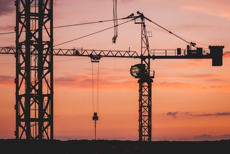 Construction crane silhouettes at sunset. Industrial background Foto de archivo