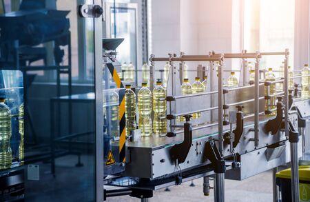 Bottling line of sunflower oil in bottles. Vegetable oil production plant. High technology. Industrial background