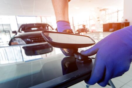 Automobile special workers replacing windscreen or windshield of a car in auto service station garage. Background Stock Photo