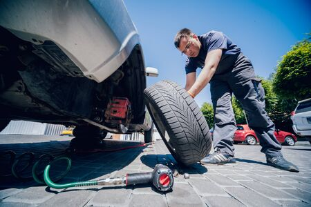 Professional car mechanic replace tire on wheel.