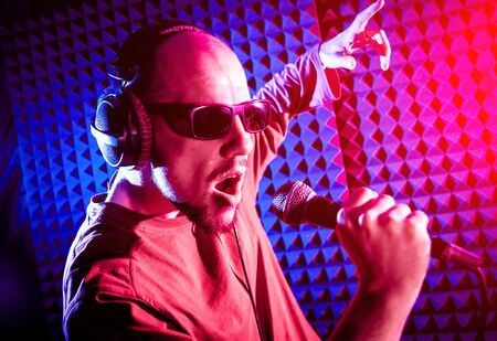 The singer sings with a microphone in the recording studio. Modern background