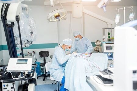 Brain surgery. Group of surgeons in operating room with surgery equipment. Modern medical background