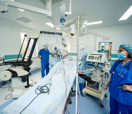 Brain surgery. Group of surgeons in operating room with surgery equipment. Modern medical background Imagens