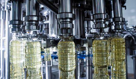 Bottling line of sunflower oil in bottles. Vegetable oil production plant. High technology. Industrial background Imagens