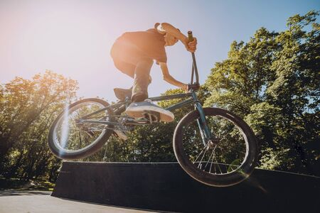 Bmx rider performing tricks at skatepark. Background