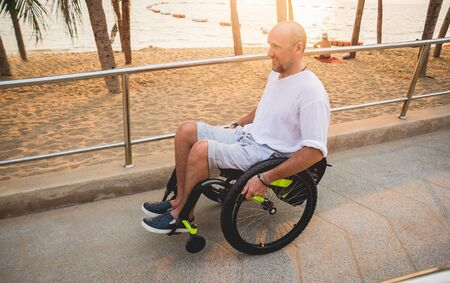 Disabled man in a wheelchair moves on a ramp to the beach. Concept background Stock Photo