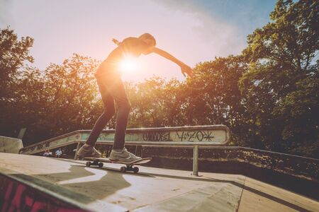 Young skateboarder in the park. Beautiful background