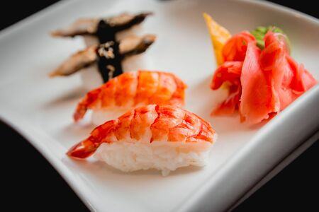 Sushi on a white plate. Rolls. The restaurant background
