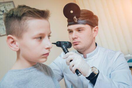Doctor examines boy ear with otoscope. Medical equipment. Standard-Bild