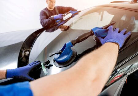 Automobile special workers replacing windscreen of a car in auto service Stock Photo