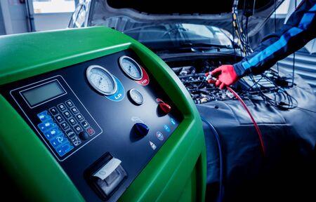 Servicing car air conditioner. Auto service station.