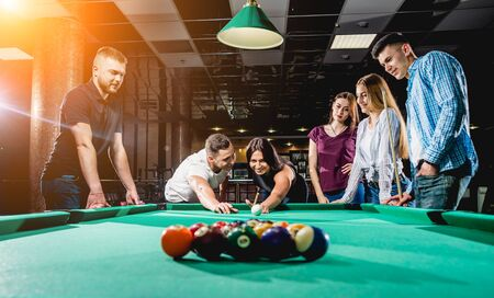 Group of young cheerful friends playing billiards.