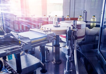Automatic labeling machine during operation. Factory for the production of vegetable oil. Industry background
