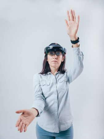 Woman wearing augmented reality goggles. White background Stockfoto