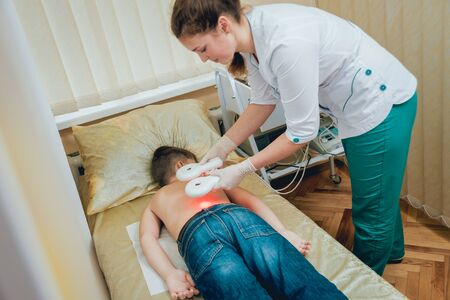 Treatment and warming-up the back of a young boy. Modern Pediatrics. Stockfoto