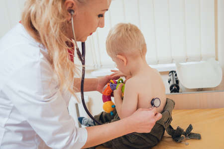 doctor woman examining heartbeat of child with stethoscope