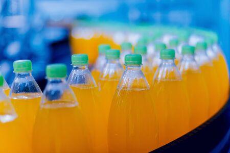 Convoyeur avec bouteilles de jus ou d'eau. Équipements d'usine de boissons. Fond