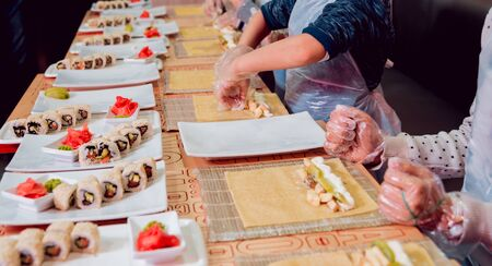 Children prepare sushi and rolls. Master-class restaurant. Background