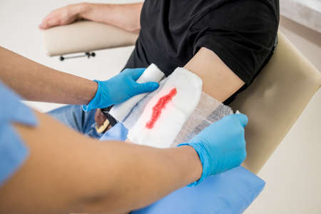Nurse dressing wound for patients hand with deep skin cutting.