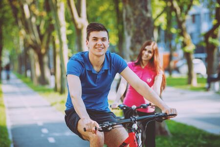 Cycling young couple. In the park. Beautiful bicycle lane.