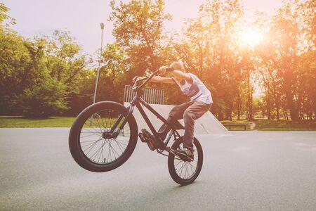 Boy riding a bmx in a park. Beautiful background